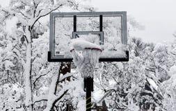 Cercle de basket-ball avec la neige dans elle après une tempête photographie stock