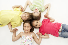 Cercle de quatre jeunes amis souriant et retenant h Photos libres de droits
