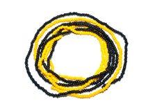 Cercle des fils avec les perles noires et oranges sur le fond blanc Photo libre de droits
