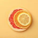 Cercles d'agrumes de citron, orange, pamplemousse sur le fond jaune Photographie stock libre de droits