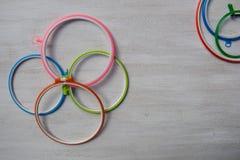 Cercles de broderie en plastique multicolores pour l'art cr?atif sur un fond clair Vue de ci-avant photo libre de droits