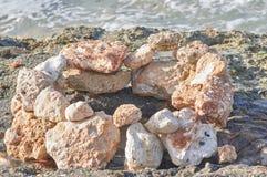 Cercles des pierres rayées sur le bord de la mer Images libres de droits