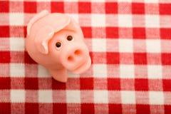 Cerdo afortunado del mazapán en mantel Fotos de archivo