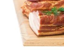 Cerdo ahumado con las especias en un tablero de madera aislado en el fondo blanco Imagenes de archivo