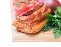 Cerdo ahumado con las especias en un tablero de madera aislado en el fondo blanco Foto de archivo libre de regalías
