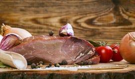 Cerdo ahumado con las hierbas, las especias, el ajo, la cebolla y los tomates Fotografía de archivo libre de regalías