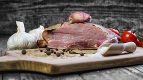 Cerdo ahumado con las hierbas, las especias, el ajo y los tomates Imagen de archivo