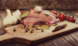 Cerdo ahumado con las hierbas, las especias, el ajo y los tomates Imagenes de archivo