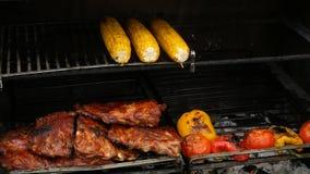 Cerdo asado a la parrilla con maíz asado y otras verduras en el festival de la comida metrajes