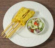 Cerdo asado a la parrilla Satay con la ensalada del pepino en el plato blanco Fotos de archivo