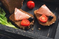 Cerdo balyk con pan negro y tomates Bocadillos con la carne en una bandeja de madera negra fotografía de archivo