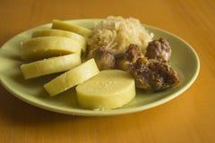 Cerdo, bolas de masa hervida y chucrut en la placa verde, comida europea media de la tradición fotos de archivo libres de regalías