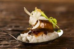 Cerdo caramelizado acompañado por el arroz del jazmín y el curry rojo en una cuchara Imagen de archivo