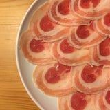 Cerdo crudo en el plato en el fondo de madera Fotos de archivo libres de regalías