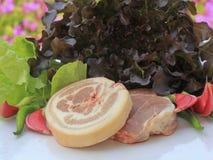 Cerdo crudo en tabla de cortar y verduras Fotos de archivo libres de regalías