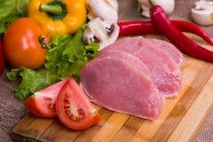 Cerdo crudo en tabla de cortar y verduras Foto de archivo libre de regalías