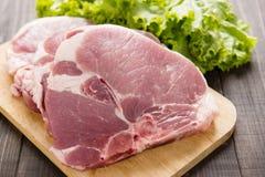 Cerdo crudo en tabla de cortar y verduras en fondo de madera Imágenes de archivo libres de regalías