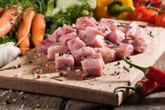 Cerdo crudo en tabla de cortar y verduras frescas Imagen de archivo libre de regalías