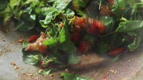Cerdo curruscante sofrito y hojas santas tailandesas de la albahaca en un wok almacen de video