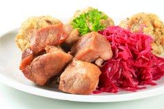 Cerdo de carne asada con las bolas de masa hervida tirolesas y el kraut rojo Imagenes de archivo