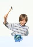 Cerdo de destrucción del ahorro del muchacho por completo del dinero con el martillo Imagen de archivo libre de regalías