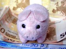 Cerdo del juguete con el dinero Fotografía de archivo