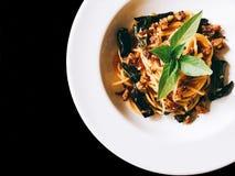 Cerdo picadito picante de los espaguetis en negro aislado foto de archivo