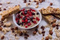 Cereálne tyčinky, ovsené vločky, lesné plody. Cereal bars, oat flakes, forest fruits in mycelium, on wooden background, healthy food Stock Images
