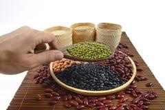 Cereais e feijões das sementes úteis para a saúde nas colheres de madeira no fundo branco Imagem de Stock