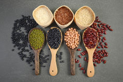 Cereais e feijões das sementes úteis para a saúde nas colheres de madeira no fundo cinzento Fotos de Stock