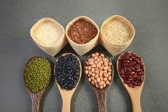 Cereais e feijões das sementes úteis para a saúde nas colheres de madeira no fundo cinzento Fotografia de Stock