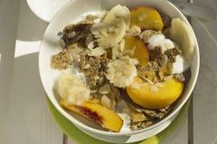 Cereais e fruto de café da manhã na madeira branca imagens de stock
