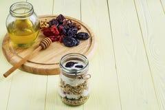 Cereais, frutos secados, mel, porcas e iogurte na placa de madeira fotografia de stock royalty free