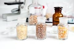 Cereais nos tubos de ensaio de vidro para a análise no laboratório foto de stock