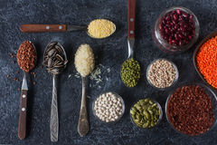 Cereais, sementes e feijões orgânicos crus em colheres e em umas bacias de madeira Foto de Stock Royalty Free