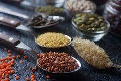 Cereais, sementes e feijões orgânicos crus em colheres e em umas bacias de madeira Imagem de Stock