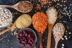 Cereais, sementes e feijões orgânicos crus em colheres e em umas bacias de madeira fotografia de stock royalty free