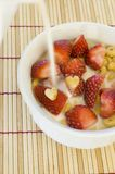 Cereal. A bowl of cereal with freshly cut red strawberries as milk is poured stock photography