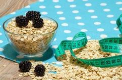 Cereal, amoras-pretas e uma fita métrica na tabela Imagem de Stock Royalty Free