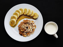 Cereal with banana topped with honey and milk one cup to health Stock Photo