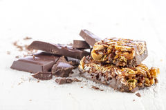 Cereal bar with chocolate. Granola bar with chocolate on white wooden background Royalty Free Stock Images
