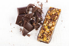 Cereal bar with chocolate. Granola bar with chocolate on white wooden background Royalty Free Stock Photography