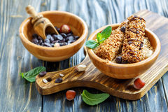 Cereal bars and chocolate drops in a wooden bowls. Royalty Free Stock Photos