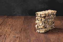 Cereal bars with nuts, berries and cinnamon on a wooden backgrou Royalty Free Stock Photography