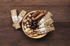 Cereal bars with nuts, berries and cinnamon on a wooden backgrou Royalty Free Stock Images