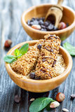 Cereal bars and oat flakes in wooden bowl. Stock Images