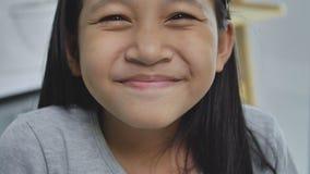 Cereal bebendo da menina asiática da criança com algum leite na mesa, filme