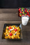 Cereal and berries in a black square bowl Morning breakfast with milk. Royalty Free Stock Image