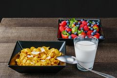 Cereal and berries in a black square bowl Morning breakfast with milk. Stock Images