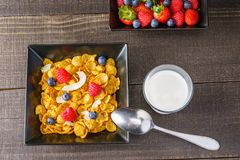 Cereal and berries in a black square bowl Morning breakfast with milk. Royalty Free Stock Photos